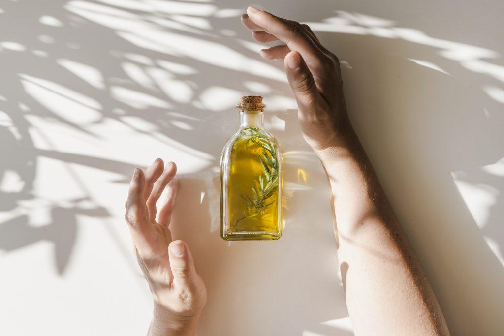 sunlight falling hands covering oil bottle white background